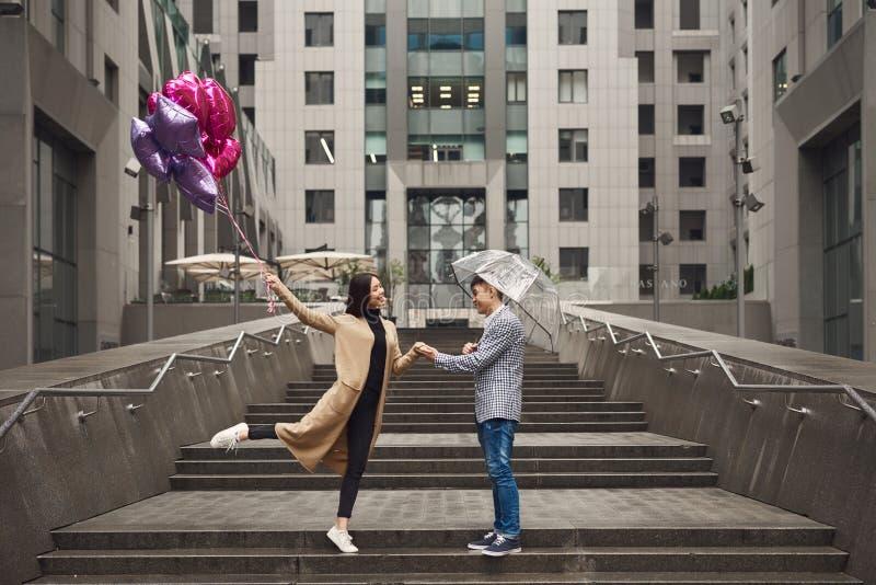 La coppia nell'amore sotto l'ombrello con i palloni passeggia lungo il viale immagine stock