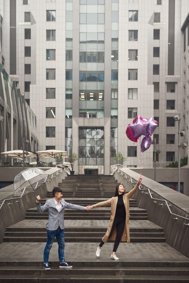 La coppia nell'amore sotto l'ombrello con i palloni passeggia lungo il viale immagini stock