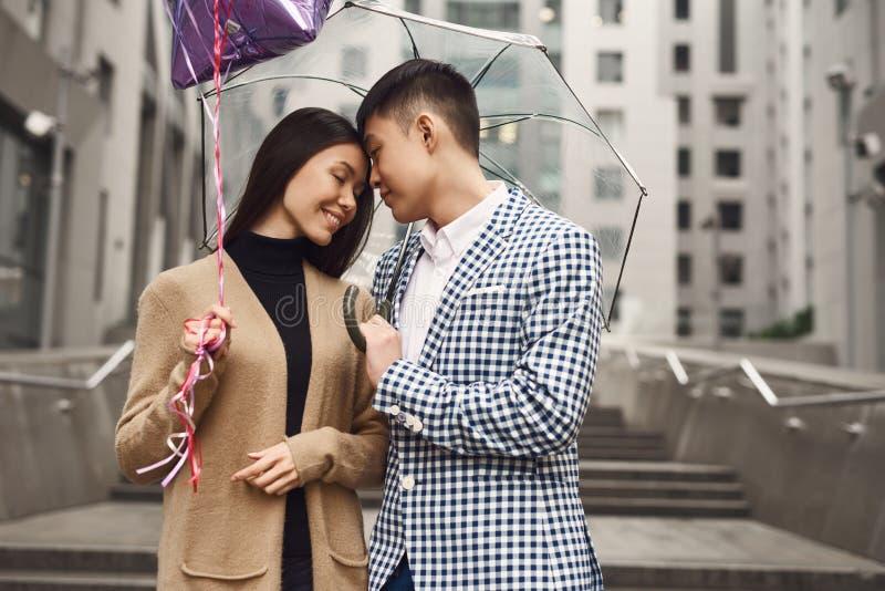 La coppia nell'amore sotto l'ombrello con i palloni passeggia lungo il viale immagine stock libera da diritti