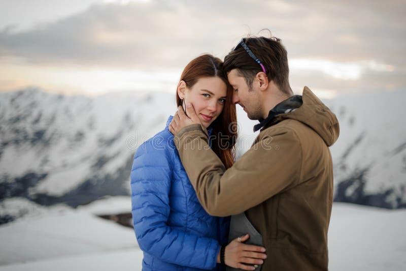 La coppia nell'amore sull'inverno vacations delicatamente abbracciando in montagne immagine stock libera da diritti