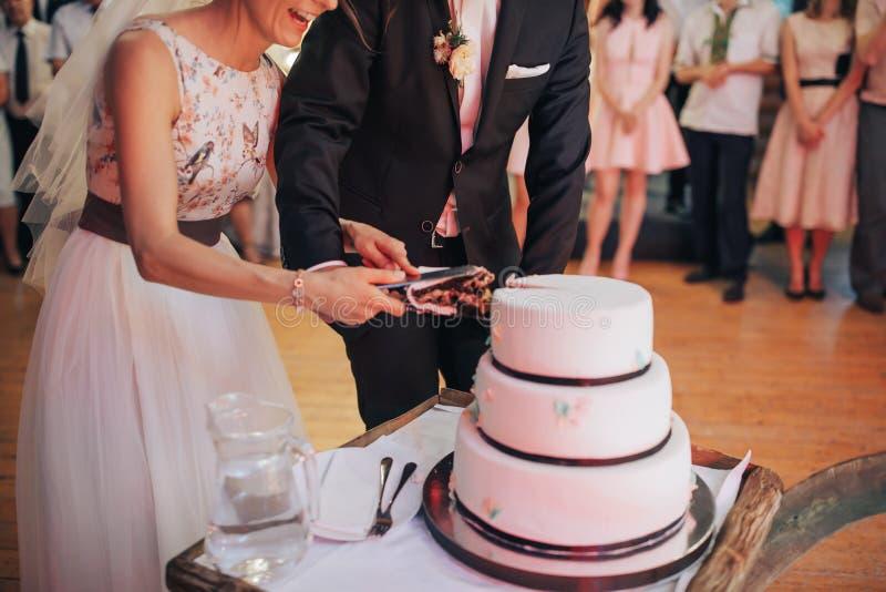 La coppia passa la torta nunziale di taglio La sposa e lo sposo felici hanno tagliato la torta nunziale immagine stock