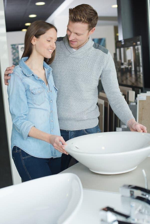 La coppia sceglie la mobilia del bagno nel deposito di miglioramento domestico fotografia stock libera da diritti