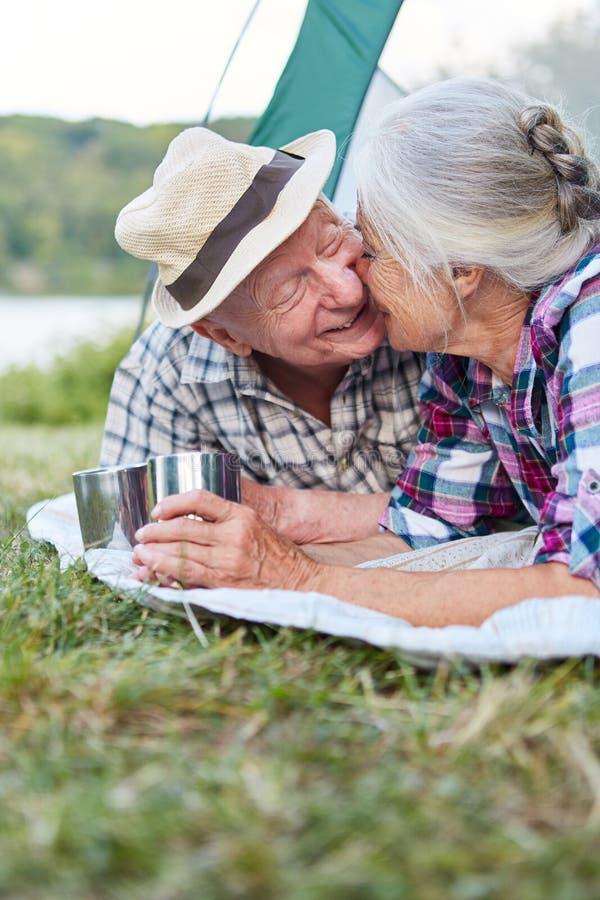 La coppia senior dà un bacio nella tenda fotografia stock