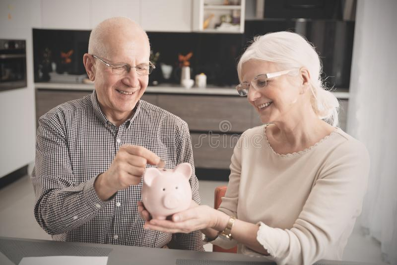 La coppia senior mette la moneta nel porcellino salvadanaio fotografie stock