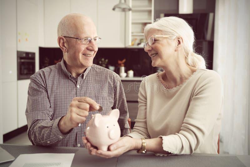 La coppia senior mette la moneta nel porcellino salvadanaio immagini stock libere da diritti