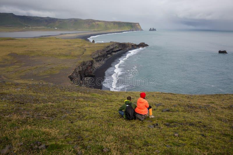 La coppia si siede su un'alta scogliera sopra il mare ed ammira la baia fotografie stock