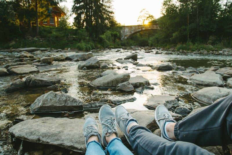 La coppia si siede vicino al fiume della montagna ed il tramonto considerare immagini stock libere da diritti
