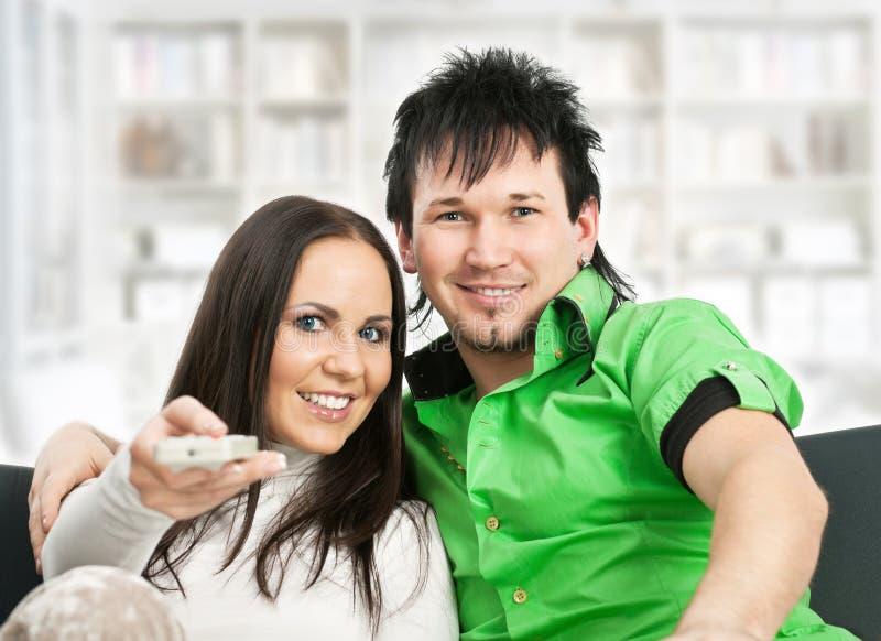 La coppia sorridente guarda la TV immagini stock