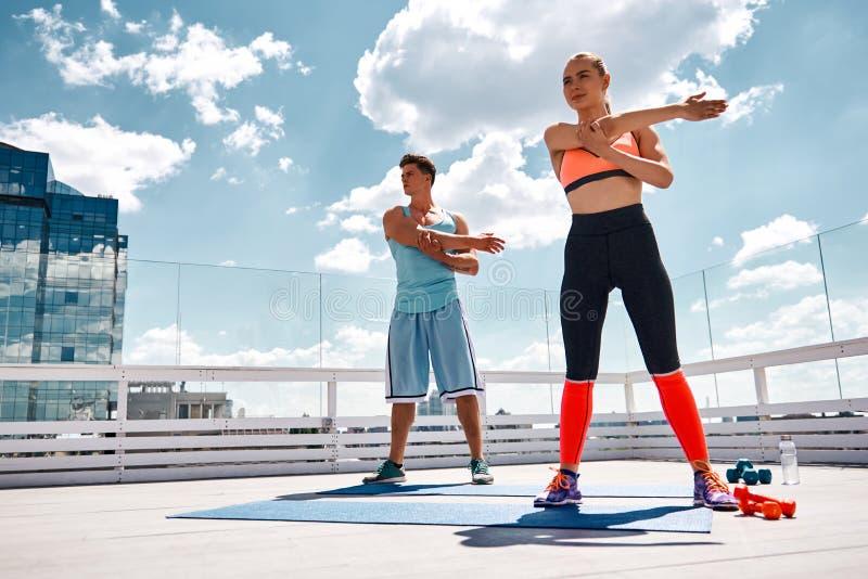 La coppia sportiva sta preparando per l'allenamento all'aperto fotografia stock