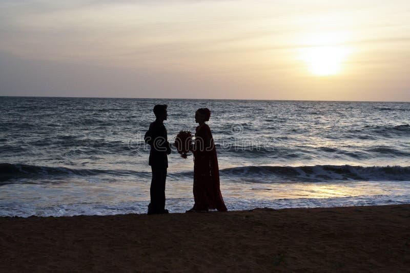 La coppia sposata sta felice alla spiaggia nel tramonto fotografia stock