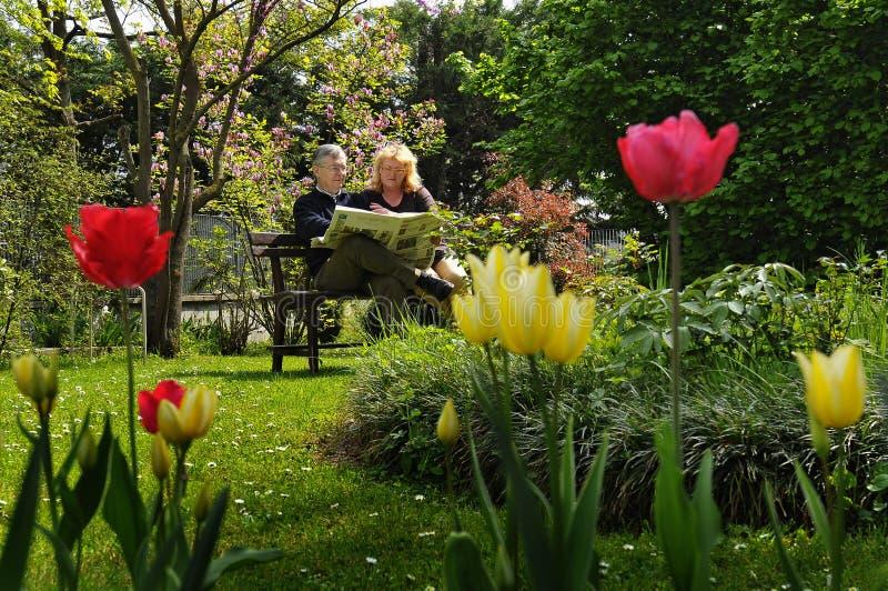 La coppia sta distendendosi nel giardino fotografia stock