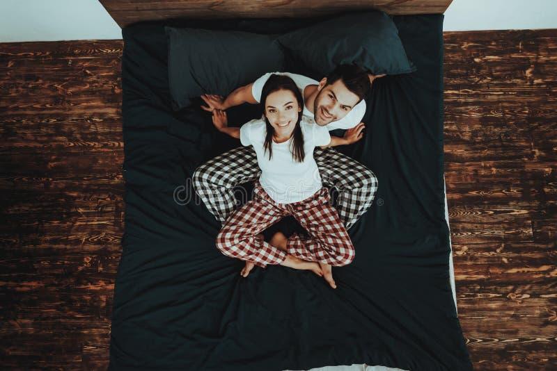 La coppia sta sedendosi sul letto e sul cercare fotografia stock