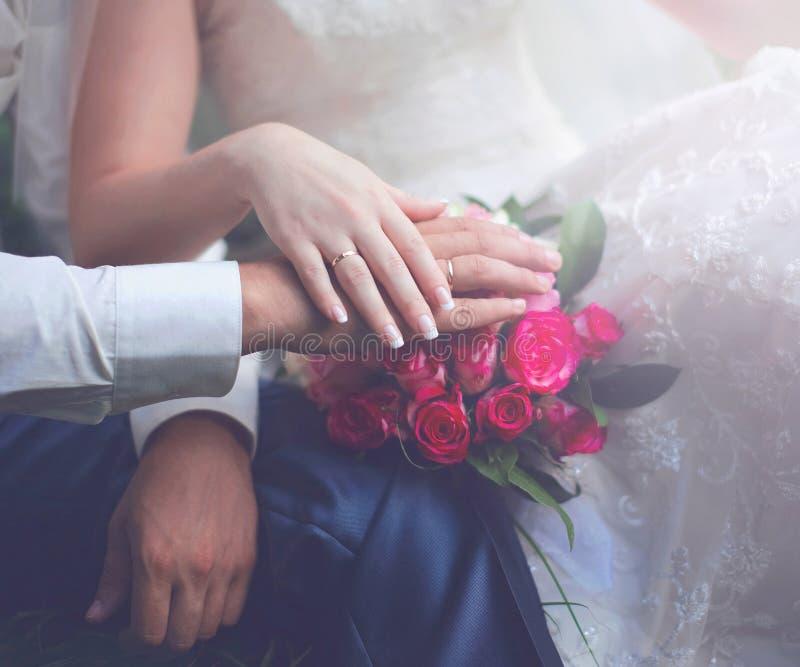 La coppia tenera di nozze, mani della sposa e sposo, mazzo delicato rosa fiorisce fotografia stock libera da diritti