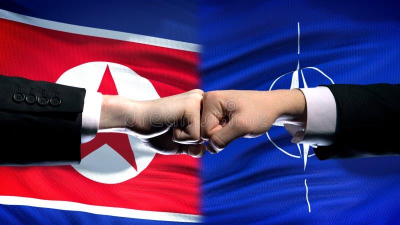 La Corée du Nord contre le conflit de l'OTAN, relations internationales, poings sur le fond de drapeau image libre de droits