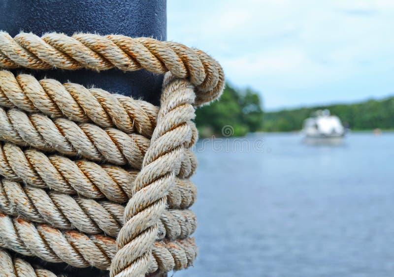 La corda del ` s della nave ha avvolto una colonna con acqua nel fondo immagine stock