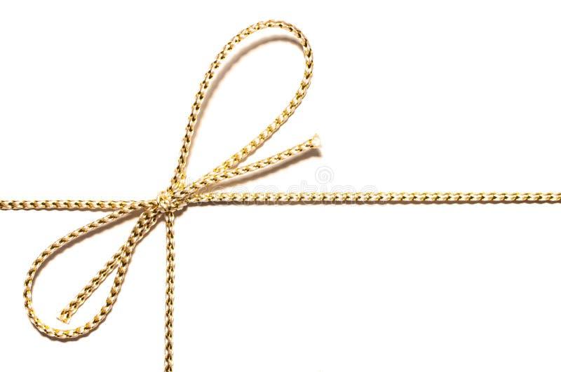 La corda dorata del raso con l'involucro annodato del nastro del regalo dell'arco per regalo di Natale con i dettagli complessi d fotografia stock libera da diritti