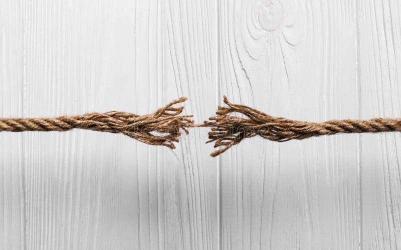 La corda ha sfilacciato circa per rompersi su fondo di legno immagine stock