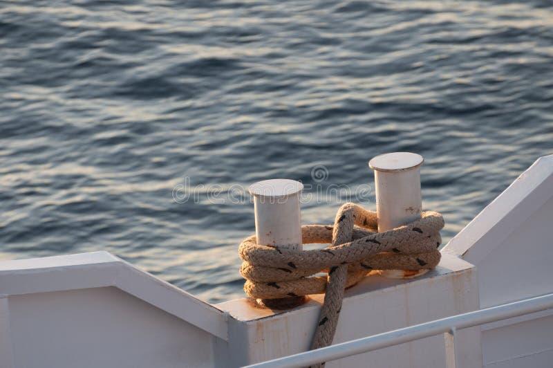 La corde a envelopp? environ deux poteaux un bateau et la mer ? l'arri?re-plan photo libre de droits