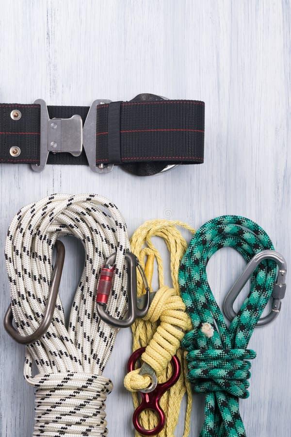 La correa del escalador con las diversas cuerdas y carabinas para la mentira del seguro en un fondo ligero fotos de archivo
