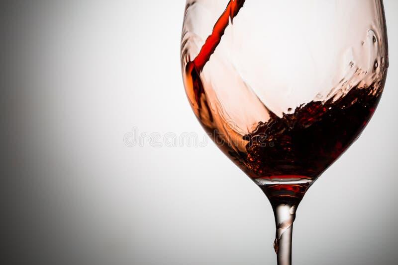 La corrente del vino rosso è versata in vetro fotografie stock