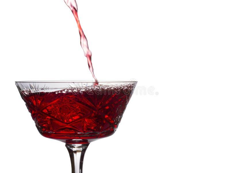 La corriente brillante del vino rojo vierte en un vidrio del vintage imágenes de archivo libres de regalías