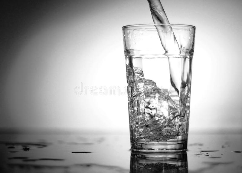 La corriente del agua cae en el vidrio fotos de archivo