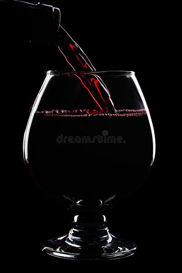 La corriente del vino rojo vierte en la copa de vino foto de archivo libre de regalías