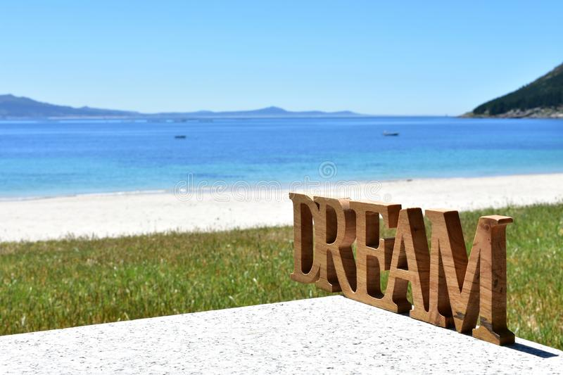 Beach with Dream wooden sign. Galicia, Spain, sunny day. stock image