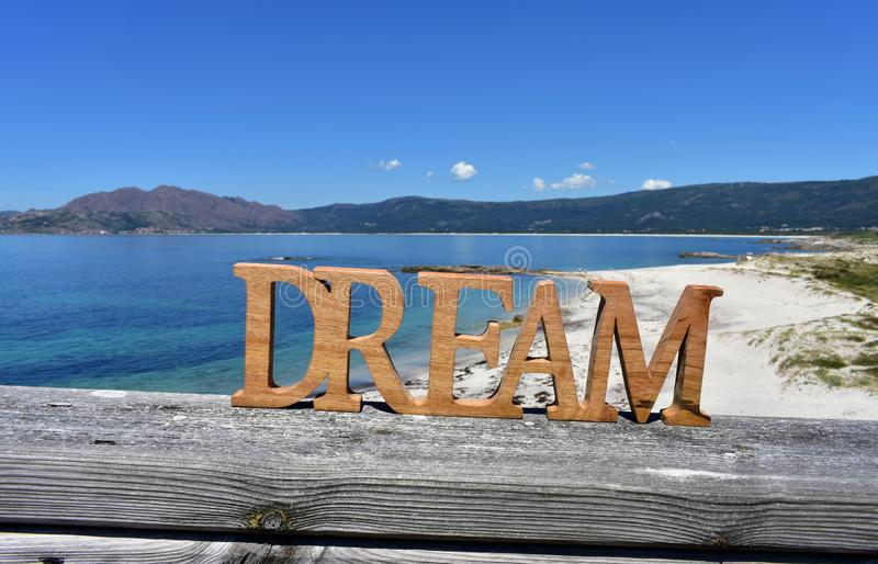 Beach with Dream wooden sign. Galicia, Spain, sunny day. stock images