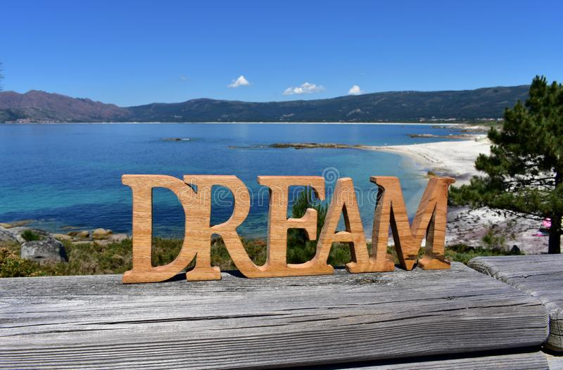 Beach with Dream wooden sign. Galicia, Spain, sunny day. royalty free stock photos