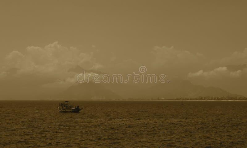 La costa di Adalia in nuvole e nella nave nella priorità alta di estate nel pomeriggio fotografia stock