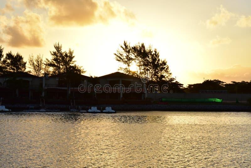 La costa y el lago de oro debajo del cielo de la puesta del sol imagen de archivo