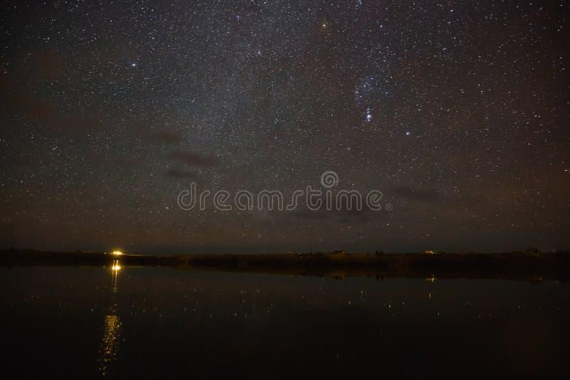 la costruzione illuminata ha riflesso in acqua e cielo stellato maestoso fotografie stock