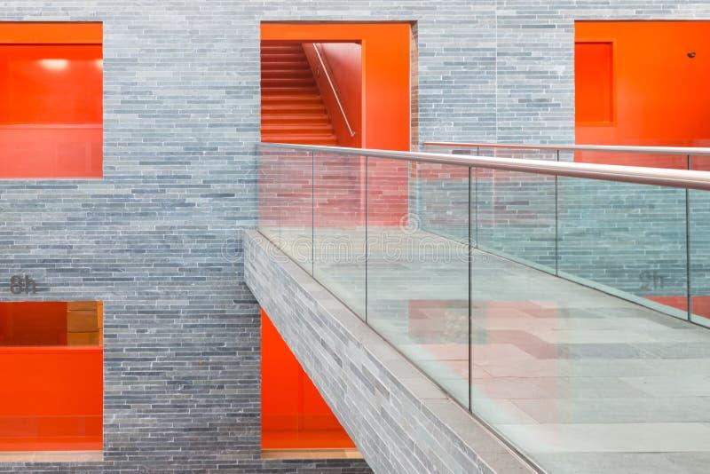La costruzione moderna della passerella con parecchi pavimenti e l'arancia ha dipinto i passaggi fotografia stock libera da diritti
