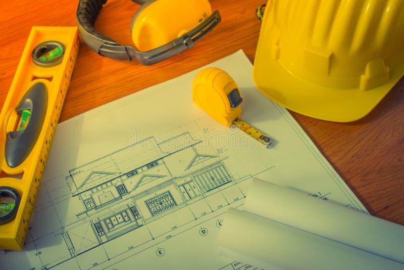 La costruzione progetta con gli strumenti gialli di disegno e del casco su bluep fotografia stock