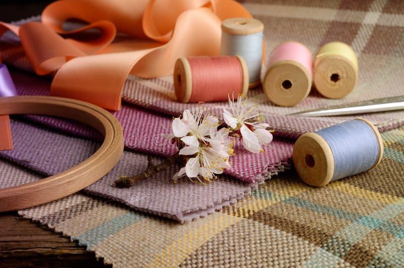 La costura de las fuentes, agujas, vintage scissors en el fondo colorido de la materia textil del yute imagenes de archivo