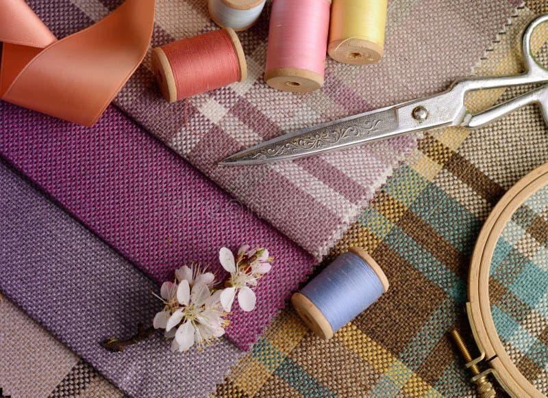 La costura de las fuentes, agujas, vintage scissors en el fondo colorido de la materia textil del yute imagen de archivo libre de regalías