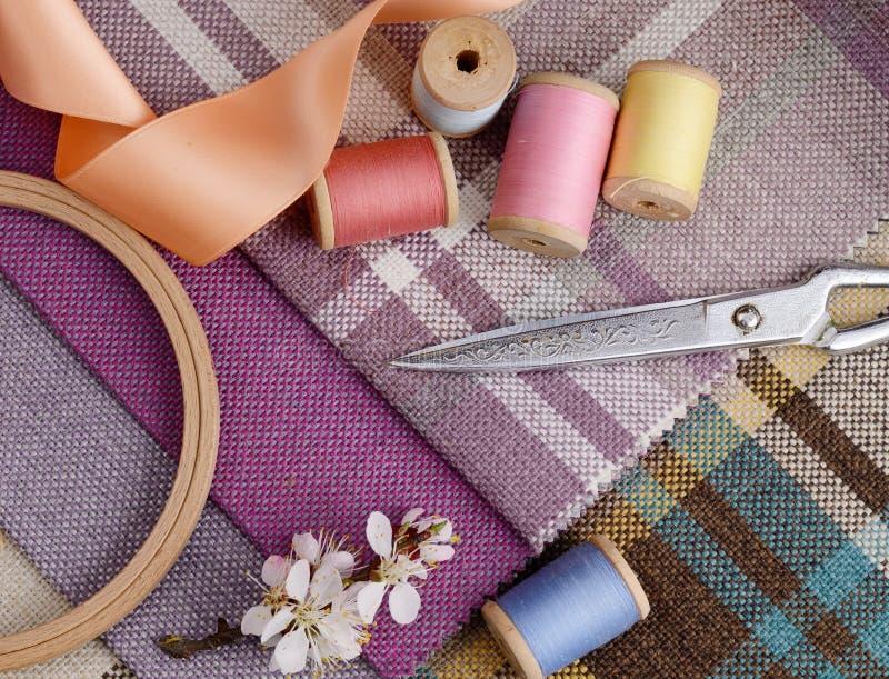 La costura de las fuentes, agujas, vintage scissors en el fondo colorido de la materia textil del yute foto de archivo libre de regalías