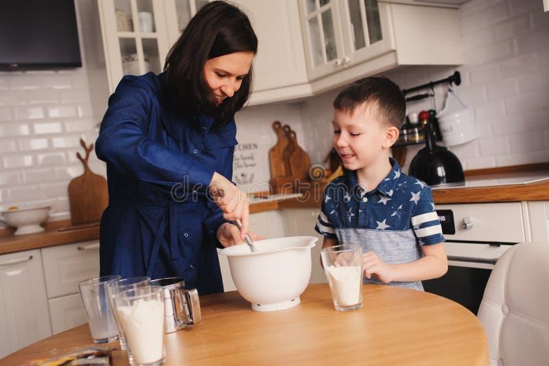 La cottura del figlio e della madre agglutina nella cucina Bloccaggio casuale di stile di vita di cottura della famiglia fotografie stock