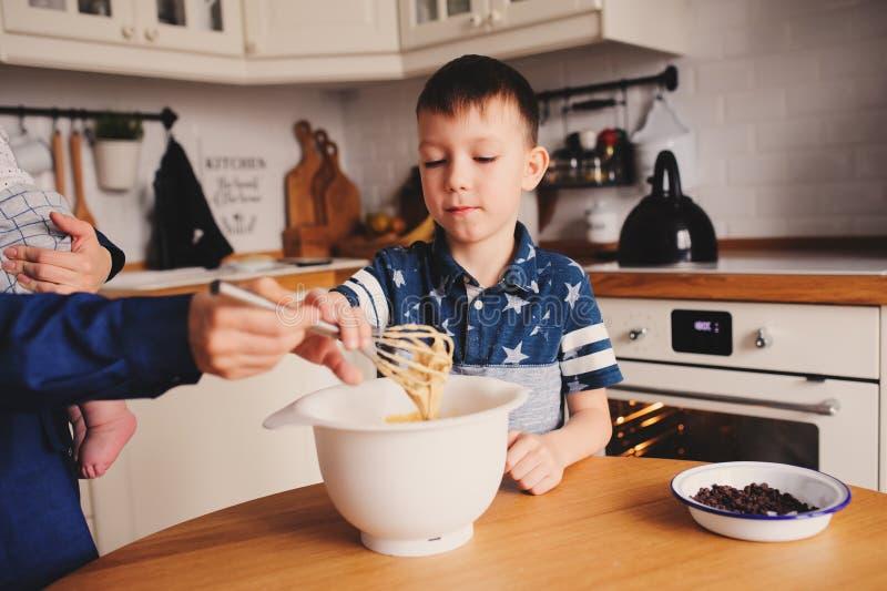 La cottura del figlio e della madre agglutina nella cucina Bloccaggio casuale di stile di vita di cottura della famiglia fotografia stock