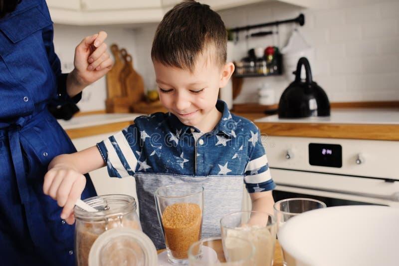 La cottura del figlio e della madre agglutina nella cucina Bloccaggio casuale di stile di vita di cottura della famiglia immagini stock