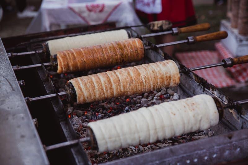 La cottura di Kurtoskalacs, il dolce ungherese tradizionale dello sputo, in un negozio di pasticceria Festival (½ del ¿ di Feszti fotografie stock libere da diritti