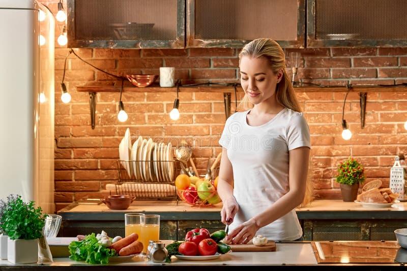 La cottura realmente sta calmando Giovane donna felice che taglia gli ortaggi freschi in cucina moderna Interiore accogliente immagini stock