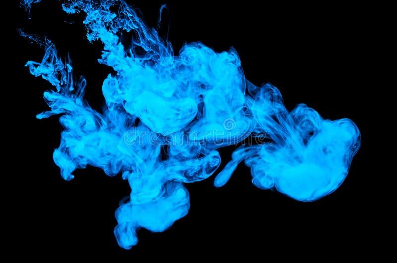 La couleur abstraite de peinture acrylique tourbillonne dans l'eau, tir de dessous, fond noir abr?gez le fond Tache d'encre image libre de droits