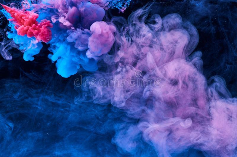 La couleur abstraite de peinture acrylique tourbillonne dans l'eau, tir de dessous, fond noir abr?gez le fond Tache d'encre image stock