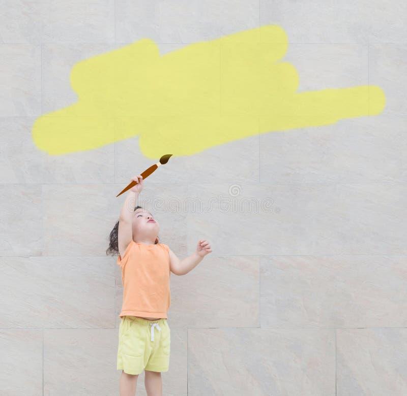 La couleur asiatique mignonne de jaune de peinture de pinceau d'utilisation d'enfant de plan rapproché pour la zone de texte au m photo libre de droits