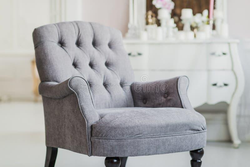 La couleur beige a tapissé la chaise dans le salon avec des fleurs photos stock