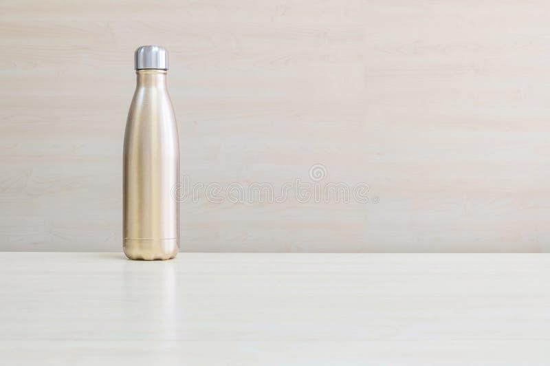 La couleur d'or de plan rapproché du flacon en aluminium pour gardent l'eau chaude sur le bureau en bois brouillé et le fond text image libre de droits