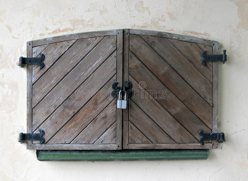 La couleur foncée naturelle a vieilli les volets lourds fermés par bois, verrouillés au grand cadenas de fer image libre de droits