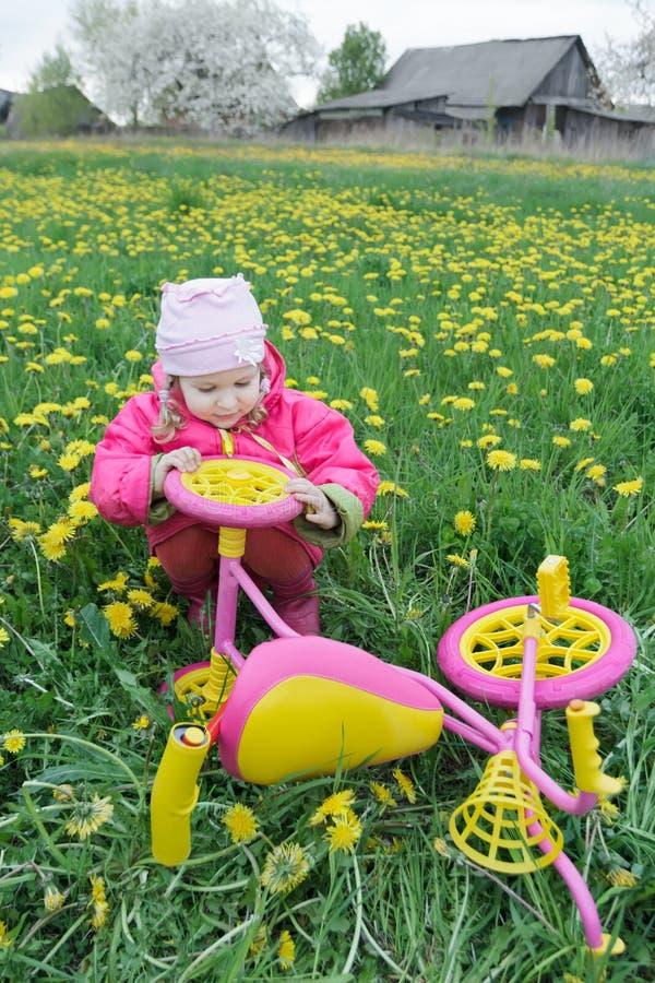 La couleur fuchsia badine le tricycle avec les roues jaunes et le véhicule l'explorant de petite fille d'enfant en bas âge image stock